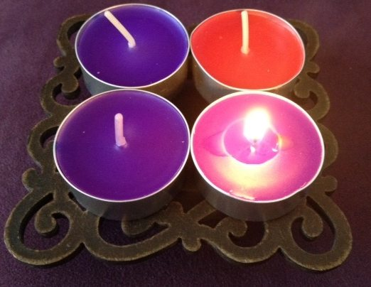 Photo of Advent wreath with first candle lit. The first purple candle symbolises hope.