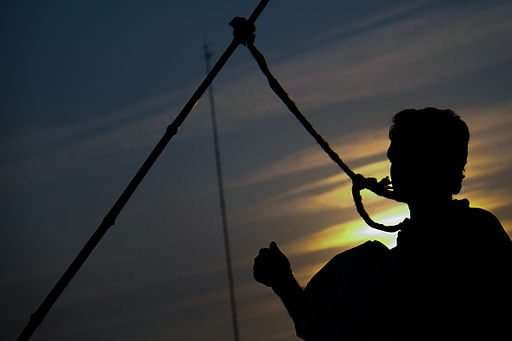 Silhouette of man with head in noose.