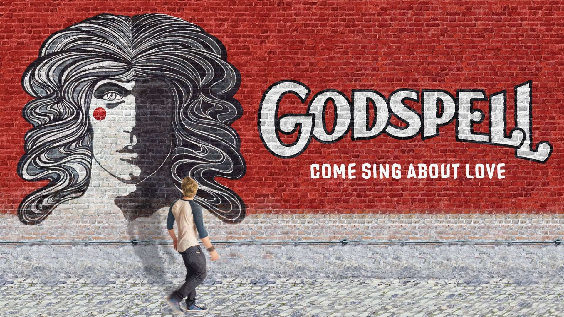 Advertising for the musical Godspell painted on a brick wall with a passer by looking at it.